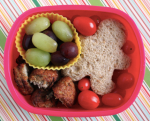 Grapes, cherry tomatoes, sandwich shaped like little man, and baked chicken nuggets.