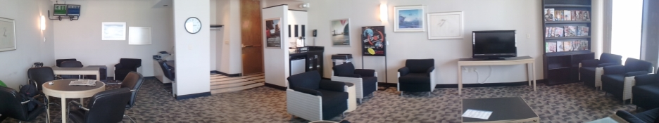 Panorama showing business center, coffee and beverage area, and lounge with TV and magazines.