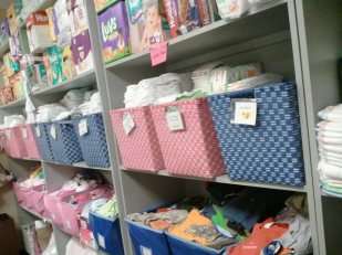 Sorted boxes of clothing, swimwear, diapers, layette sets stand at the ready for filling client needs.