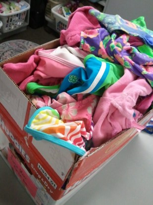This box of donations will soon be sorted by size and season and organized on the shelves.