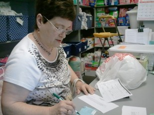 JoAnne fills out a checklist to make sure every item is included for a new mom.
