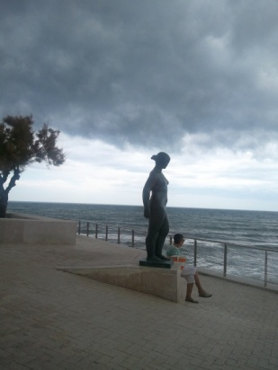 A looming storm gives drama and significance to beachside statuary.